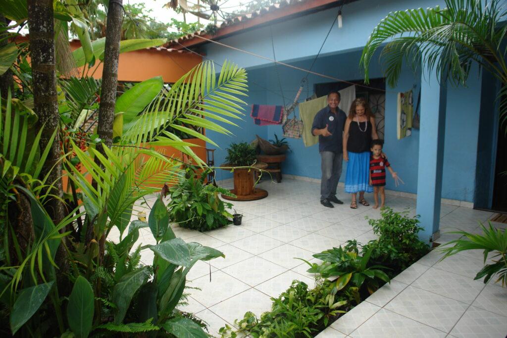 Antonia Melo com o irmão e o neto na área de sua casa